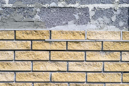 Wall cladding with decorative bricks, front view. Material for decorating the wall of house or fence Фото со стока