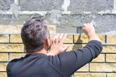 Man decorates the facade of the fence with decorative torn bricks. Work at home during quarantine. Do it yourself.