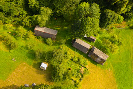 Aerial drone view of old wooden hut on mountain slope. Stable for cattle and barn near hut, green well-groomed yard Фото со стока