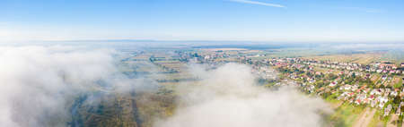 Aerial drone view of scenic countryside in autumn sunny and misty day. Birds eye view of traditional Ukrainian village