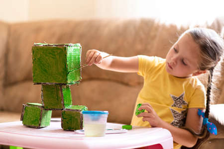 Little girl paints a paper toy. Create a game hero with your own hands. Home leisure and self-development.