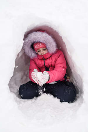 Cute caucasian girl plays with snow in her hiding place. Winter entertainment.