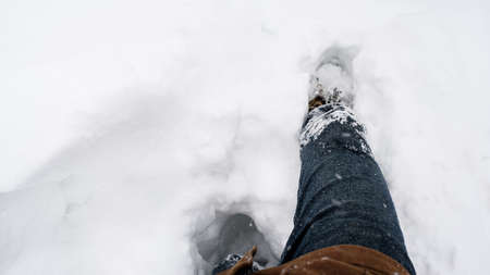 Man to knees in snow tramples the path. Winter snowstorm