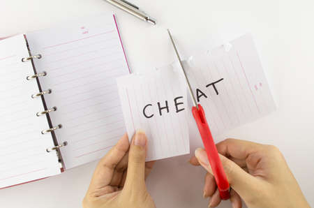 dutiful: Persons who were cutting paper labeled  cheat  Stock Photo
