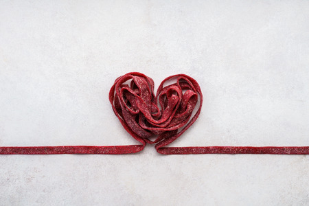 Red beetroot pasta shaped as heart. Valentines Day greeting or invitational card concept. Stock Photo