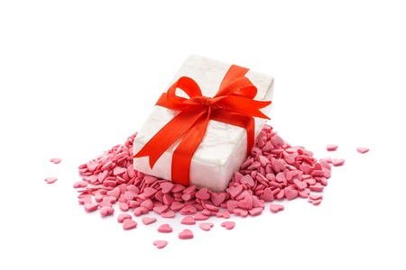 Gift box with red ribbon lying on a pile of heart shaped candies. Isolated. Valentines Day concept.