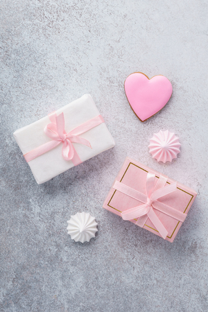 Valentine's Day sale layout design. Gift boxes with pink ribbon, heart shaped mousse cake, cookies and meringues. Space for text. Flat lay. Zdjęcie Seryjne