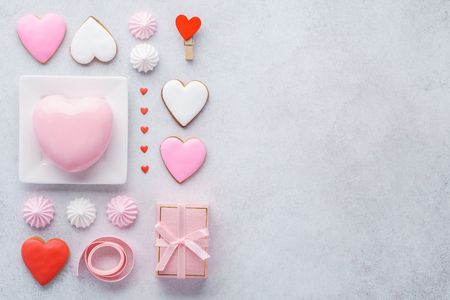 Valentine's Day composition. Wrapped gift box, pink ribbon, heart shaped mousse cake, glazed cookies and mini meringues on light background. Flat lay. Stok Fotoğraf