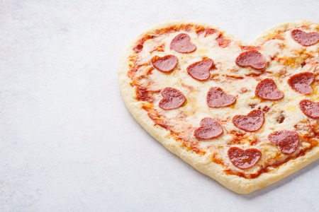 Heart shaped pizza with pepperoni, tomatoes and mozzarella. Valentines day food concept.