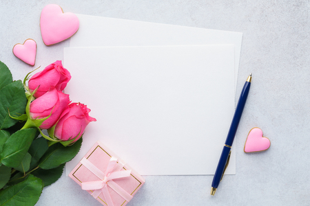 Happy Valentines Day greeting card with empty list of paper, pink roses, gift box, heart shaped cookies and pen. Space fot text.