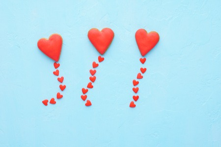 Red heart shaped balloons made of cookies and candy fly out. Valentines Day and love concept. Blue background. Top view.