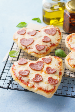 Baked heart shaped homemade pepperoni mini pizza. Happy Valentines day. Romantic dinner concept. Banque d'images