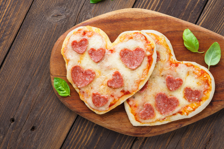 Heart shaped mini pizza. Valentine's day romantic menu mockup for restaurant or delivery. Space for text. Wooden background.