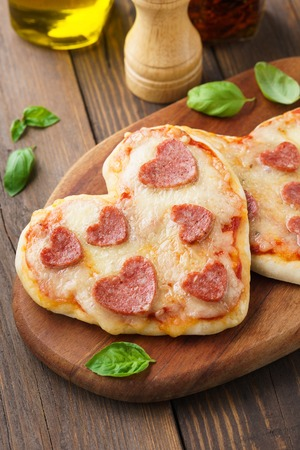 Small heart shaped pizzas with mozzarella cheese, pepperoni, tomato and basil on wooden serving board. 版權商用圖片