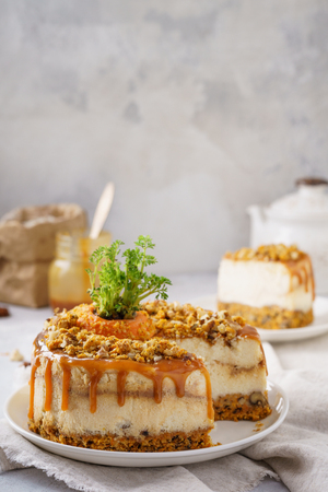 Carrot cheesecake with walnuts and caramel and cut piece of cake on a plate.