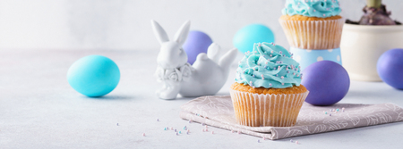 Easter vanilla cupcakes, colored eggs, cute bunny and hyacinth in a flower pot. Holiday banner concept.