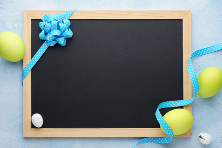 Easter frame with painted green eggs and empty chalkboard. Background with copy space. Stock Photo