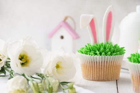 Easter cupcake decorated with bunny ears and grass for dessert and flowers.