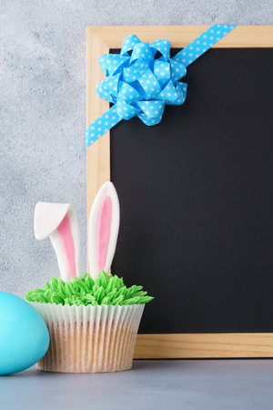 Easter background with bunny ears cupcake, egg and empty chalkboard for text. Stock Photo