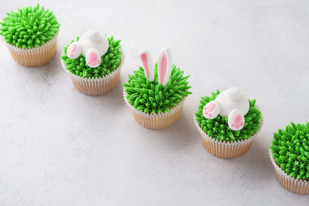 Homemade Easter cupcakes in a row. Decorated as grass, bunny butt and bunny ears. 免版税图像