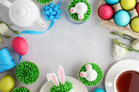 Easter frame background with bunny cupcakes, tea and painted eggs. Top view, copy space. Stock Photo