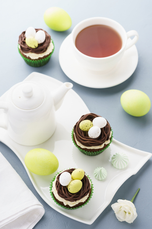 Easter chocolate cupcakes decorated with nest and candy eggs for dessert. Holiday table setting. Stock Photo