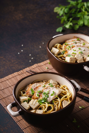 Asian miso ramen noodles with chicken and tofu. Dark background. 版權商用圖片