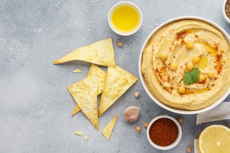 Traditional hummus bowl served with tortilla chips. Middle eastern food concept. Top view.