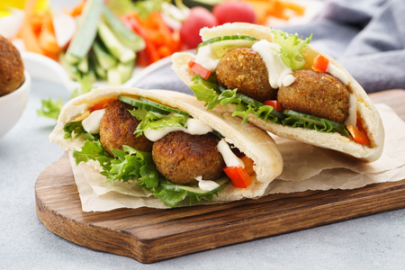 Healthy vegetarian falafel pita with fresh vegetables, lettuce and sauce. Stock Photo