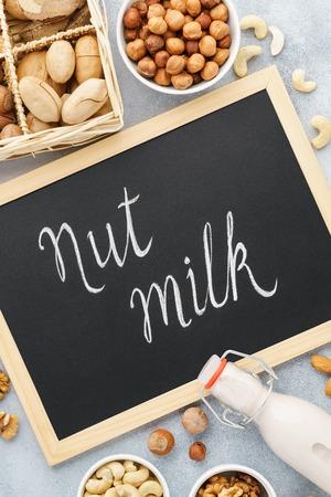 Nut milk and ingredients. Milk alternatives. Chalkboard lettering. Almond, walnut, hazelnut, pecan and brazil nut