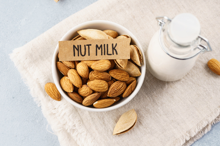 Bottle of nut milk and raw almonds. Dairy free and lactose free milk.
