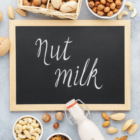 Nut milk and various nuts around chalkboard. Vegan dairy free, no lactose milk concept.