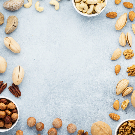 Frame made of different raw nuts. Background with copy space. Top view.