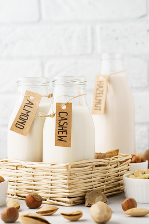 Various nut milk in bottles with tags - almond, cashew, hazelnut and raw ingredients.