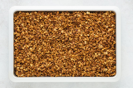 Homemade healthy granola with oats, nuts and honey on a tray. Overhead.