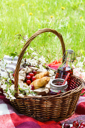 Picnic basket with food on green sunny lawn. Croissants, cherry berries and juice, flowers.