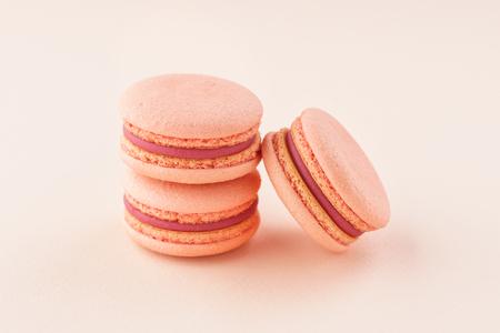 Pila de macarons rosados con relleno de bayas sobre fondo del mismo color. Monocromo. Foto de archivo