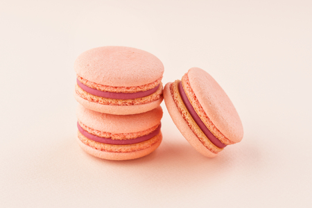 Stack of pink macarons with berry filling on same color background. Monochrome.