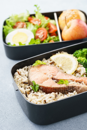 Healthy and nutritious lunch or snack boxes with food - fish, fresh fruits and vegetables.