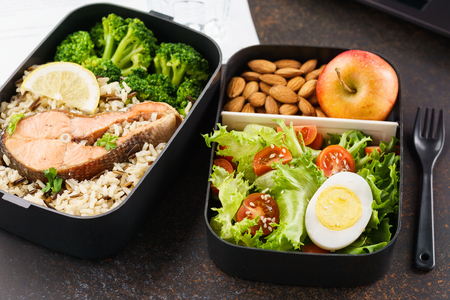 Healthy lunch at office workplace. Takeaway lunch boxes with nutrition food - fish, vegetables and fruits at working desk with laptop.