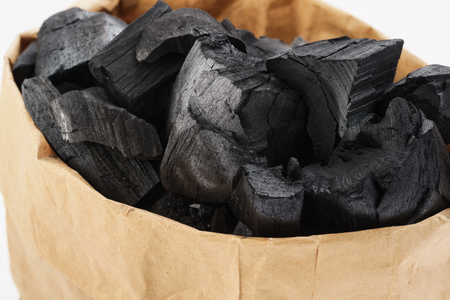 Black charcoal in a paper bag. Charcoal for igniting fire in a grill. 免版税图像