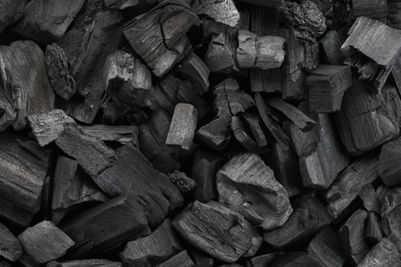 Black charcoal texture background. Close-up shot. Top view.