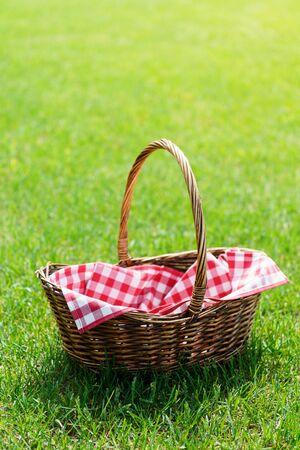 Pusty kosz piknikowy z czerwoną serwetką w kratkę na trawie. Ciepłe naturalne światło słoneczne. Miejsce na tekst.