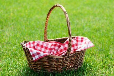 Leerer Picknickkorb auf grünem sonnigem Rasen. Picknick Vorbereitung.