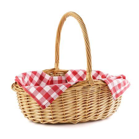 Cesta de mimbre vacía con mantel a cuadros rojo para picnic. Aislado en blanco. Foto de archivo