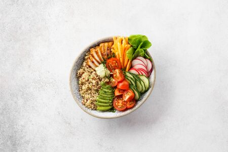 Healthy buddha bowl lunch with grilled chicken or turkey, quinoa and fresh vegetables. Copy space. Top view.