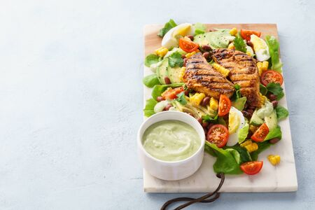 Grilled chicken breast and fresh vegetable salad with ranch dressing. Healthy balanced lunch. Copy space. Stock fotó