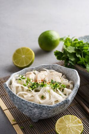 Pho ga, vietnamese chicken rice noodle soup and ingredients.