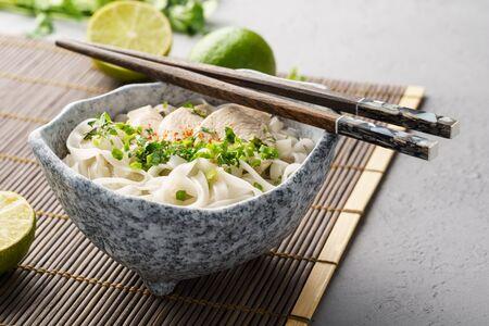 Pho ga, wietnamska zupa z makaronem ryżowym w misce z pałeczkami. Zdjęcie Seryjne