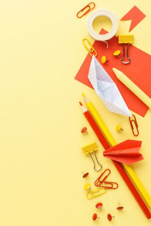Various red and yellow stationery over yellow background. Back to school creative mockup with copy space.